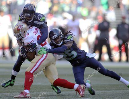 Seattle Seahawks free safety Earl Thomas (29) and cornerback Richard Sherman (25) bring down San Francisco 49ers running back Shaun Draughn (24) at CenturyLink Field in Seattle, Washington on November 22, 2015.  The Seahawks beat the 49ers 29-13.