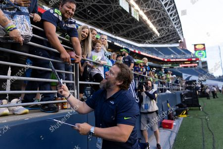 Stock Photo of Seattle Seahawks general manager John Schneider signs autographs for fans before an NFL preseason football game against the Los Angeles Chargers, in Seattle. The Seahawks won 27-0