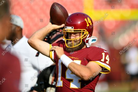 Washington Football Team quarterback Ryan Fitzpatrick (14) warms up prior to the start of a preseason NFL football game against the Baltimore Ravens, in Landover, Md
