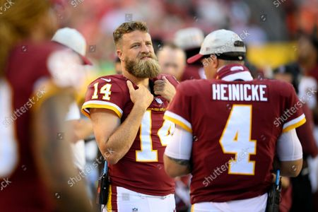 Washington Football Team quarterback Ryan Fitzpatrick (14) looks on during the first half of a preseason NFL football game against the Baltimore Ravens, in Landover, Md