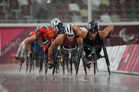 Manuela Schaer of Switzerland, right, and Tatyana McFadden of the United States, center, compete in the women's 1500m T54 final during the Tokyo 2020 Paralympics Games at the National Stadium in Tokyo, Japan