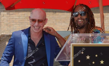 Armando Christian Perez (L), aka Pitfall reacts to comments by Lil John during an unveiling ceremony honoring him with the 2,584th star on the Hollywood Walk of Fame in Los Angeles on July 15, 2016.