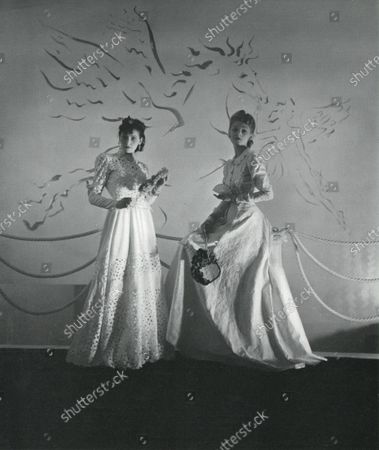 Two models posed in Elizabeth Arden's new Paris salon with a gold Pegasus and Cupid mural by Vertes cut into the white plaster wall behind. On the models are dresses by Balenciaga of (left) old-fashioned embroidered white lawn, with a peplumed jacket, and (right) embroidered white glazed chintz.