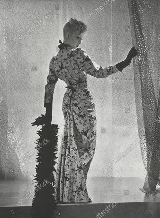 """Model wearing a patterned Balenciaga evening gown in pale blue printed moire, in the """"Polonaise Silhouette,"""" holding a feather boa and standing in front of a dotted curtain."""