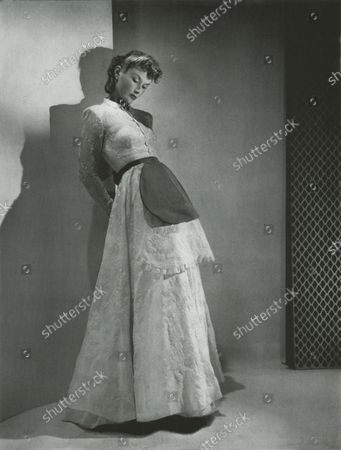 Stock Picture of Model in studio wearing an embroidered handkerchief linen dress by Balenciaga, buttoned up to the neck, with two aprons tied at the waist, one of same fabric, and the other topmost one of preiwinkle faille. Jewels by Boucheron.