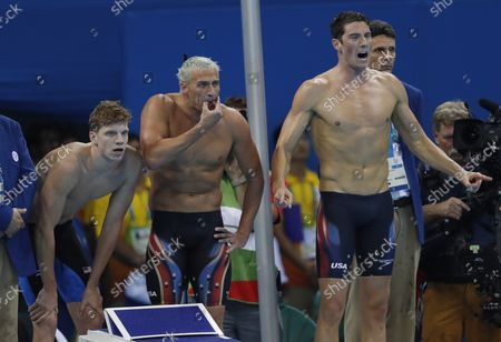 Conor Dwyer, Ryan Lochte and Townley Haas of the United States react as Michael Phelps swims the final leg of the Men's 4x200m freestyle relay at the Olympic Aquatics Stadium at the 2016 Rio Summer Olympics in Rio de Janeiro, Brazil, on August 9, 2016. The United States won the gold medal and Michael Phelps wins his 21st Gold Medal.