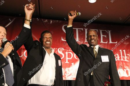 """Greg Marecek, President of the St. Louis Sports Hall of Fame (L) raises the arm of former heavyweight boxing champion Leon Spinks while brother Michael Spinks raises his arm after the two are declared """"Legends of Boxing,"""" during the St. Louis Sports Hall of Fame Enshrinement ceremonies in Fronentec , Missouri on September 22, 2016."""