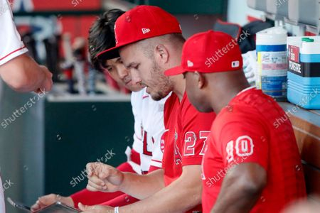 Los Angeles Angels' Mike Trout, center, talks with Shohei Ohtani, left, and Justin Upton on the bench before a baseball game against the New York Yankees in Anaheim, Calif