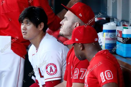 Los Angeles Angels' Shohei Ohtani, left, looks up at a coach with Mike Trout, center, with Justin Upton on the bench before a baseball game against the New York Yankees in Anaheim, Calif