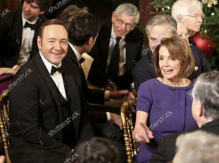 Actor Kevin Spacey (L) and representative Nancy Pelosi (R) wait for the beginning of an event for the 2016 Kennedy Center Honorees, in the East Room of the White House, December 4, 2016. The honorees include pianist Martha Argerich, actor Al Pacino, singer Mavis Staples, singer James Taylor and Eagles band members Don Henley, Timothy B. Schmit, Joe Walsh.