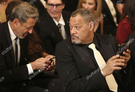Actor Jeff Goldblum  (L) and actor Laurence Fishburne (R) wait for the beginning of an event for the 2016 Kennedy Center Honorees, in the East Room of the White House, December 4, 2016. The honorees include pianist Martha Argerich, actor Al Pacino, singer Mavis Staples, singer James Taylor and Eagles band members Don Henley, Timothy B. Schmit, Joe Walsh.