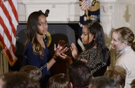 Stock Photo of President Barack Obama's daughters Malia Obama (L) and Sasha Obama look on during an event where he presented the Medal of Freedom to Vice President Joe Biden in the State Dinning room of the White House on January 12, 2017 in Washington, DC.