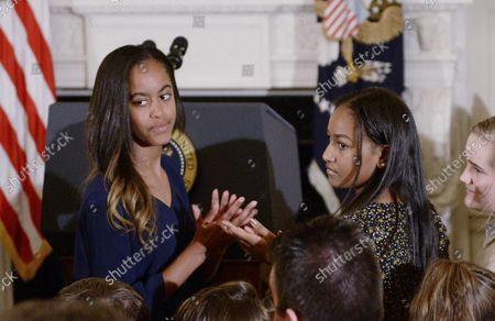 Stock Picture of President Barack Obama's daughters Malia Obama (L) and Sasha Obama look on during an event where he presented the Medal of Freedom to Vice President Joe Biden in the State Dinning room of the White House on January 12, 2017 in Washington, DC.