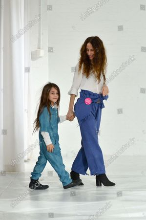 Designer Mara Hoffman walks off stage with her daughter after her fashion show at New York Fashion Week: The Shows at Shop Studios on February 13, 2017 in New York City.