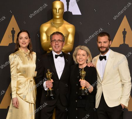 Production designer David Wasco (2nd from L) and set decorator Sandy Reynolds-Wasco (2nd from R), winners of the award for Production Design for 'La La Land', and presenters Dakota Johnson (L) and Jamie Dornan appear backstage during the 89th annual Academy Awards at Loews Hollywood Hotel in the Hollywood section of Los Angeles on February 26, 2017.