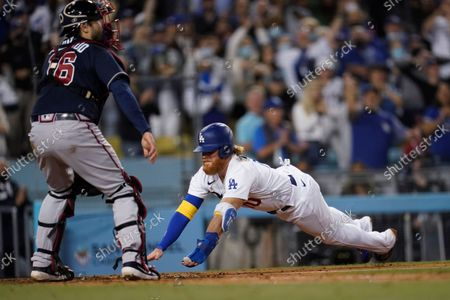 Los Angeles Dodgers' Justin Turner, right, scores past Atlanta Braves catcher Travis d'Arnaud on a single by AJ Pollock during the eighth inning of a baseball game, in Los Angeles