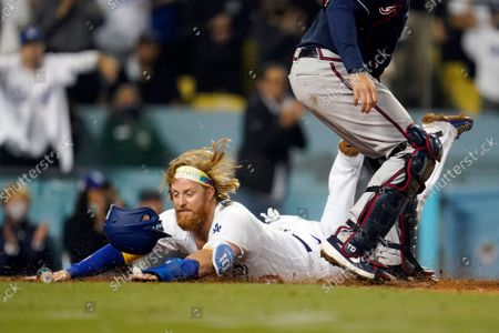 Los Angeles Dodgers' Justin Turner scores past Atlanta Braves catcher Travis d'Arnaud on a single by AJ Pollock during the eighth inning of a baseball game, in Los Angeles