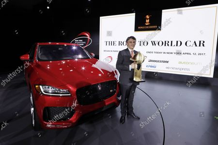 CEO of Jaguar Land Rover Dr. Ralf Speth holds the 2017 'World Car of the Year' Trophy in front of the winning Jaguar F-Pace car at the 2017 New York International Auto Show at the Jacob K. Javits Convention Center in New York City on April 12, 2017. The first New York Auto Show was held in 1900 and it was the first auto show ever held in North America. About 1 million visitors are expected to attend the show.