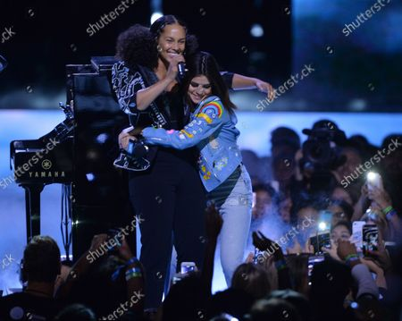 Stock Photo of Singer Alicia Keys is joined onstage by show host Selena Gomez during We Day California at The Forum in Inglewood, California on April 27, 2017. WE Charity, formerly known as Free The Children, is a worldwide development charity and youth empowerment movement founded in 1995 by human rights advocates Craig Kielburger and Marc Kielburger.