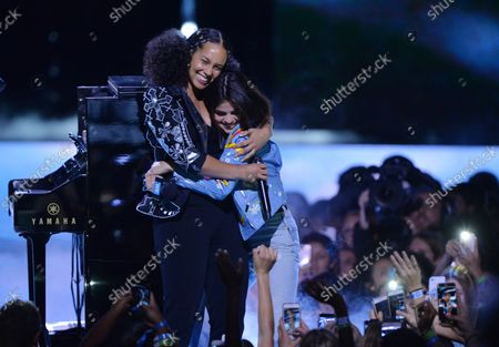 Singer Alicia Keys is joined onstage by show host Selena Gomez during We Day California at The Forum in Inglewood, California on April 27, 2017. WE Charity, formerly known as Free The Children, is a worldwide development charity and youth empowerment movement founded in 1995 by human rights advocates Craig Kielburger and Marc Kielburger.