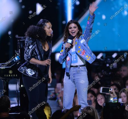 Stock Image of Singer Alicia Keys is joined onstage by show host Selena Gomez during We Day California at The Forum in Inglewood, California on April 27, 2017. WE Charity, formerly known as Free The Children, is a worldwide development charity and youth empowerment movement founded in 1995 by human rights advocates Craig Kielburger and Marc Kielburger.
