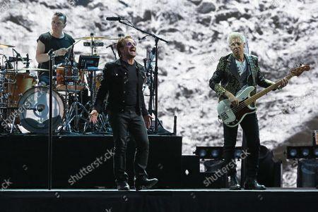 U2 members Larry Mullen Jr (L), Bono (C) and Adam Clayton perform in concert at the Stade de France near Paris on July 25, 2017.
