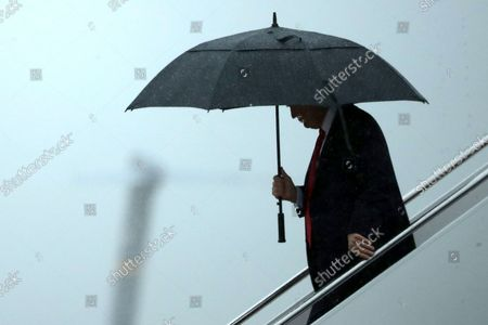 U.S. President Donald Trump uses an umbrella after stepping out of Air Force One July 28, 2017 at Joint Base Andrews, Maryland. Trump announced via Twitter that he had fired Chief of Staff Reince Priebus and was replacing him with Homeland Security Secretary John Kelly.