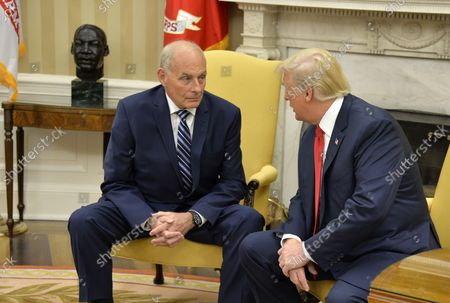 President Donald Trump (R) confers with the new White House Chief of Staff John Kelly after he was sworn in, in the Oval Office of the White House, July 31, 2017, in Washington, DC. Kelly, a retired Marine Corps general and formerly secretary of the Department of Homeland Security, replaces Reince Priebus.