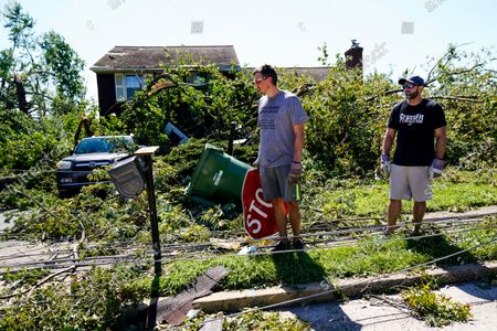 Stock Photo of Sean Powers, center, accompanied by Mike Gabriel, holding a sign that blew in from some other location inspects the destruction around his home in Fort Washington, Pa. in the aftermath of downpours and high winds from the remnants of Hurricane Ida that hit the area