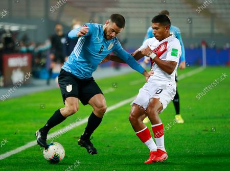 Uruguay's Nahitan Nandez, left and Peru's Edison Flores battle for the ball during a qualifying soccer match for the FIFA World Cup Qatar 2022, in Lima, Peru