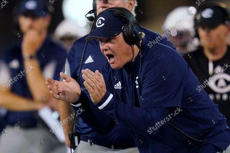 Stock Photo of Davis coach Dan Hawkins applauds during the second half of the team's NCAA college football game against Tulsa, in Tulsa, Okla