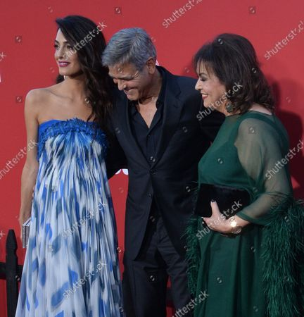 """Executive producer/writer/director George Clooney, his wife, human rights attorney Amal Clooney and her mother Baria Alamuddin (R) attend the premiere of the motion picture crime thriller """"Suburbicon"""" at the Regency Village Theatre in the Westwood section of Los Angeles on October 22, 2017. Storyline: Suburbicon is a peaceful, idyllic suburban community with affordable homes and manicured lawnsÉthe perfect place to raise a family, and in the summer of 1959, the Lodge family is doing just that. But the tranquil surface masks a disturbing reality, as husband and father Gardner Lodge (Matt.Damon) must navigate the townÕs dark underbelly of betrayal, deceit, and violence. This is a tale of.very flawed people making very bad choices. This is Suburbicon."""