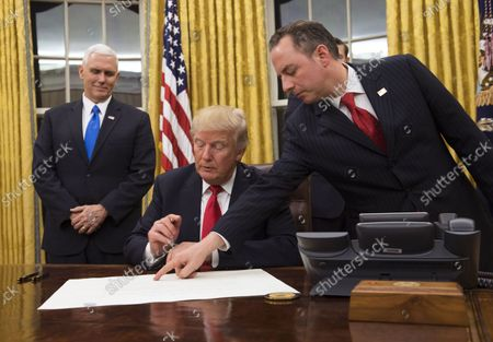 President Donald Trump prepares to sign a confirmation for Defense Secretary James Mattis as his Chief of Staff Reince Priebus points to the order while Vice President Mike Pence watches, at the White House in Washington, D.C. on January 20, 2017.