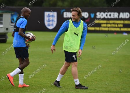 Sir Mo Farah gets the ball off of Olly Murs of England during a training session