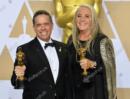 Filmmakers Lee Unkrich (L) and Darla K. Anderson, winners of the award for Best Animated Feature Film for 'Coco,' appear backstage with their Oscars during the 90th annual Academy Awards at Loews Hollywood Hotel in the Hollywood section of Los Angeles on March 4, 2018.