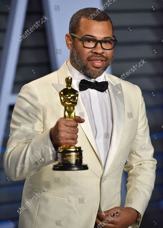 Writer and director Jordan Peele holds his Oscar for Best Original Screenplay as he arrives for the Vanity Fair Oscar Party at the Wallis Annenberg Center for the Performing Arts in Beverly Hills, California on March 4, 2018.