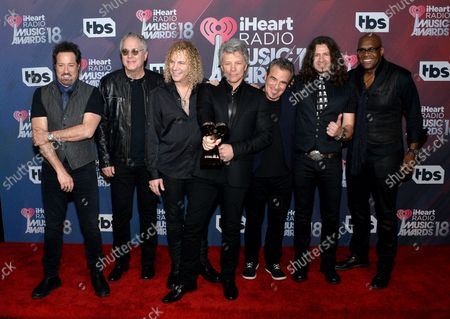 (L-R) John Shanks, Hugh McDonald, David Bryan, Jon Bon Jovi, Tico Torres, Phil X, and Everett Bradley of Bon Jovi, recipients of the Icon Award, appear backstage during the iHeartRadio Music Awards at The Forum in Inglewood, California on March 11, 2018. Turner's TBS, TNT, and truTV channels broadcasted the ceremony live from The Forum.