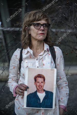 Kim Russell holds a photo of Phillip Rau at a demonstration  at City Hall across from the NRA Convention at Kay Bailey Hutchison Convention Center in Dallas on May 4, 2018. Phillip Rau was on a date with Russel when the restaurant they were eating at was robbed. Both Russel and Rau were shot. Rau died from his injuries.