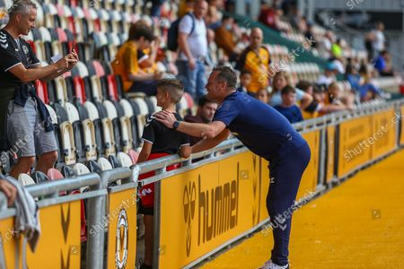 Newport County's Manager Michael Flynn poses for a photograph with a young Fan before the EFL Sky Bet League 2 match between Newport County and Leyton Orient at Rodney Parade, Newport