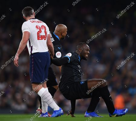 Roberto Carlos helps Usain Bolt of World XI off of the floor during the Soccer Aid for UNICEF 2021 match