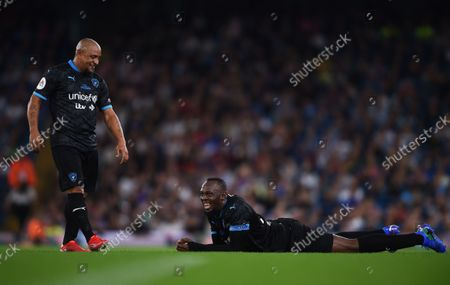 Roberto Carlos checks on Usain Bolt of World XI while he's on the floor during the Soccer Aid for UNICEF 2021 match