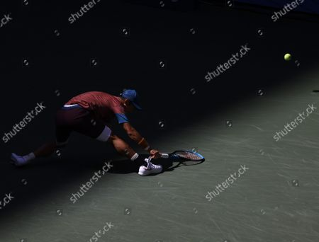 Kei Nishikori of Japan reaches but fails to return the ball to Novak Djokovic of Serbia in the first set in Arthur Ashe Stadium in the third round of the 2021 US Open Tennis Championships at the USTA Billie Jean King National Tennis Center on Saturday, September 4, 2021 in New York City.