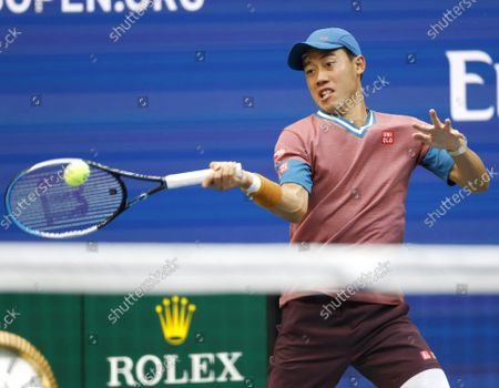 Kei Nishikori of Japan returns a ball to Novak Djokovic of Serbia  before losing in 4 sets in Arthur Ashe Stadium in the third round of the 2021 US Open Tennis Championships at the USTA Billie Jean King National Tennis Center on Saturday, September 4, 2021 in New York City.