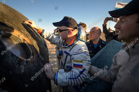 Expedition 56 Flight Engineer and Soyuz Commander Oleg Artemyev of Roscosmos signs the outside of the Soyuz MS-08 spacecraft just minutes after he, Expedition 56 Commander Drew Feustel of NASA, and Flight Engineer Ricky Arnold of NASA, landed in a remote area near the town of Zhezkazgan, Kazakhstan on October 4, 2018. Feustel, Arnold, and Artemyev are returning after 197 days in space where they served as members of the Expedition 55 and 56 crews onboard the International Space Station. NASA