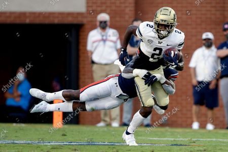 Stock Image of Akron running back Anthony Williams Jr. (2) is tack;ed from behind by Auburn linebacker Owen Pappoe during the first half of an NCAA college football game, in Auburn, Ala