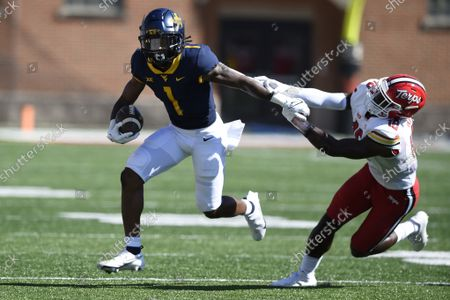 Maryland's Jordan Mosely, right, grabs West Virginia's Winston Wright Jr. in the first half of an NCAA college football game, in College Park, Md