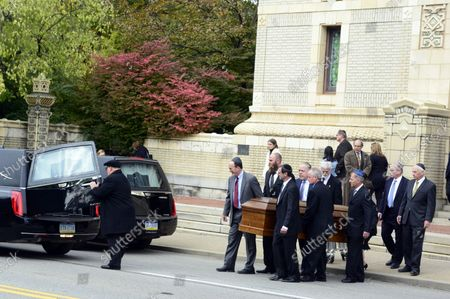 Pallbearers carry a casket to the hearse  at the funeral services for Cecil and David Rosenthal at the Rodef Shalom Temples in Pittsburgh on October 30, 2018. The brothers where victims of the mass shooting where a gunman kill 11 people at the Tree of Life Synagogue.
