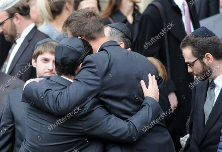 Stock Image of Mourners embrace  outside the Rodef Shalom Temples following the funeral services for brothers Cecil and David Rosenthal in Pittsburgh on October 30, 2018. The brothers where victims of the mass shooting where a gunman kill 11 people at the Tree of Life Synagogue.