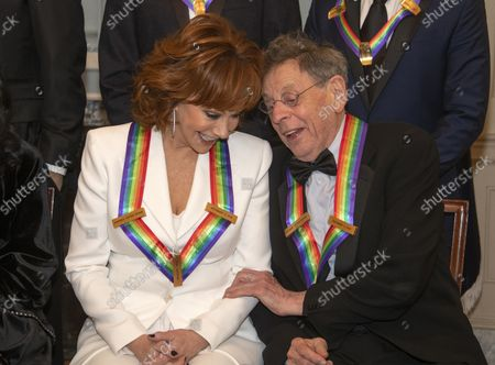 Reba McEntire, left, and Philip Glass two of the recipients of the 41st Annual Kennedy Center Honors, converse as they pose for a group photo following a dinner hosted by United States Deputy Secretary of State John J. Sullivan in their honor at the US Department of State in Washington, D.C. on Saturday, December 1, 2018.  The 2018 honorees are: singer and actress Cher; composer and pianist Philip Glass; Country music entertainer Reba McEntire; and jazz saxophonist and composer Wayne Shorter. This year, the co-creators of Hamilton, writer and actor Lin-Manuel Miranda; director Thomas Kail; choreographer Andy Blankenbuehler; and music director Alex Lacamoire will receive a unique Kennedy Center Honors as trailblazing creators of a transformative work that defies category.