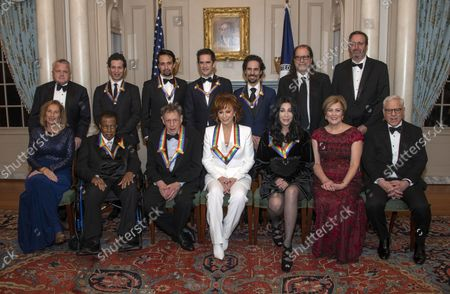 The recipients of the 41st Annual Kennedy Center Honors pose for a group photo following a dinner hosted by United States Deputy Secretary of State John J. Sullivan in their honor at the US Department of State in Washington, D.C. on Saturday, December 1, 2018.  From left to right back row: Deputy Secretary of State Sullivan, Thomas Kail, Lin-Manuel Miranda, Andy Blankenbuehler, Alex Lacamoire, Glenn Weiss, and Ricky Kirshner, Executive Producers with White Cherry. Front row, left to right: Grace Rodriguez, Wayne Shorter, Philip Glass, Reba McEntire, Cher, Deborah F. Rutter and David M. Rubenstein.  The 2018 honorees are: singer and actress Cher; composer and pianist Philip Glass; Country music entertainer Reba McEntire; and jazz saxophonist and composer Wayne Shorter. This year, the co-creators of Hamilton, writer and actor Lin-Manuel Miranda; director Thomas Kail; choreographer Andy Blankenbuehler; and music director Alex Lacamoire will receive a unique Kennedy Center Honors as trailblazing creators of a transformative work that defies category.
